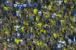 Maccabi TA fans cheering near end of soccer match.