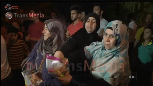 Abu Srour's relatives hand out candies to celebrate his shaheed status.