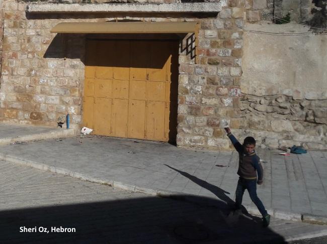 kid throwing stones in Hebron