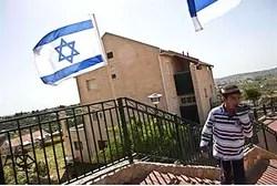 A boy walks near Israeli flags in Ulpana