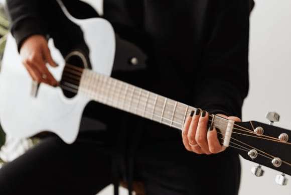 https://www.pexels.com/photo/crop-anonymous-female-artist-playing-classic-guitar-at-home-4472111/