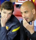Barcelona's second coach Tito Vilanova talks to Pep Guardiola before their match against Athletic Bilbao at Spanish King's Cup soccer match final at the Vicente Calderon stadium in Madrid