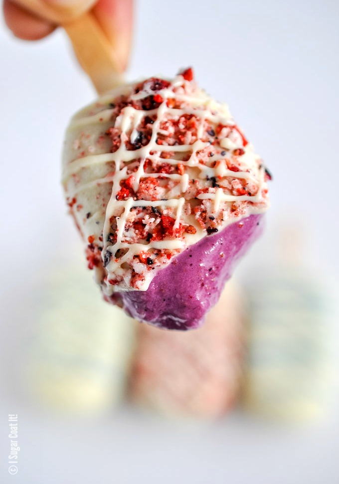 Blueberry Coconut Popsicles are a delightful blend of berries, coconut yogurt and milk dipped in decadent white chocolate and toasted coconut and freeze-dried berries.