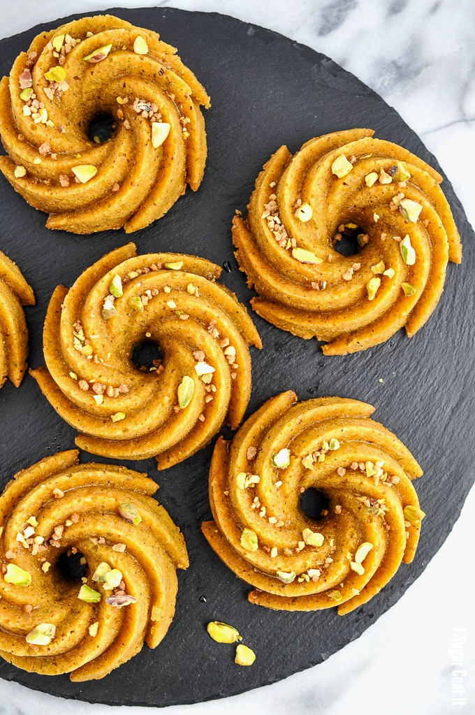 Flavour-packed, melt-in-your-mouth Pistachio Orange Caramel Mini Bundt Cakes, drizzled with orange caramel and topped with candied pistachio.
