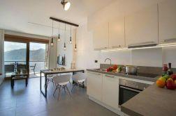 Woonkamer met open keuken en uitzicht op het Comomeer