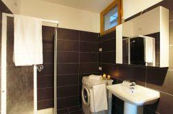 Badkamer met douche en wasmachine