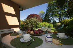 Overdekt terras met uitzicht op de grote omheinde prive-tuin