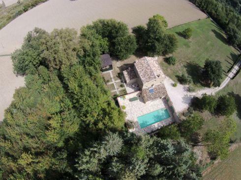 Het huis met ommuurde binnenplaats, prive-zwembad en grote tuin gezien vanuit de lucht