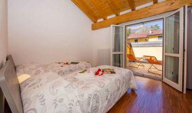 Slaapkamer 2 met twee 1-persoonsbedden en terras