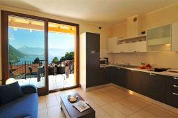 Woonkamer met volledig uitgeruste open keuken en schuifdeuren naar het terras