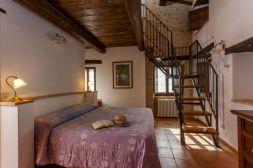 Vakantiehuis Noce   Slaapkamer met 2-persoonsbed en trap naar de vide met de derde slaapkamer