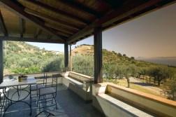 Groot overdekt terras met uitzicht op de olijfboomgaard en de zee