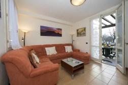 Appartement Orchidea 3| Woonkamer met grote bank en toegang tot het terras