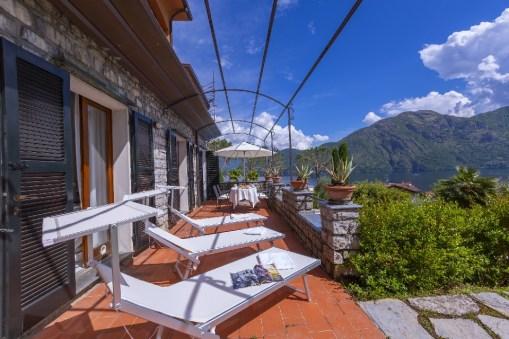 Groot prive-terras met sun loungers en aan achterin een tafel en stoelen met parasol