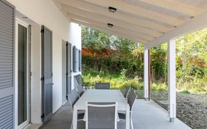 Groot overdekt terras met zicht op het zwembad en de tuin huis 1