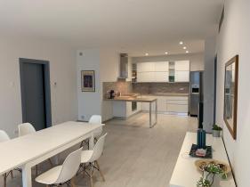 De woonkamer met volledig uitgeruste open keuken