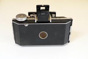 La fotocamera a dorso chiuso, si noti il pulsante di sblocco del nottolino