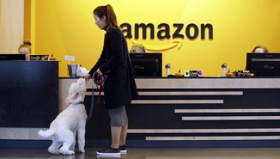 FILE - In this Wednesday, Oct. 11, 2017, file photo, an Amazon employee gives her dog a biscuit as the pair head into a company building, where dogs are welcome, in Seattle. Amazon announced Thursday, Jan. 18, 2018, that it has narrowed its hunt for a second headquarters to 20 locations, concentrated among cities in the U.S. East and Midwest. Toronto made the list as well, keeping the companys international options open. (ANSA/AP Photo/Elaine Thompson, File) [CopyrightNotice: Copyright 2017 The Associated Press. All rights reserved.]