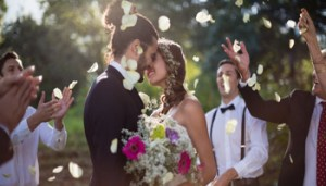 Affectionate bride and groom kissing on their wedding day in park