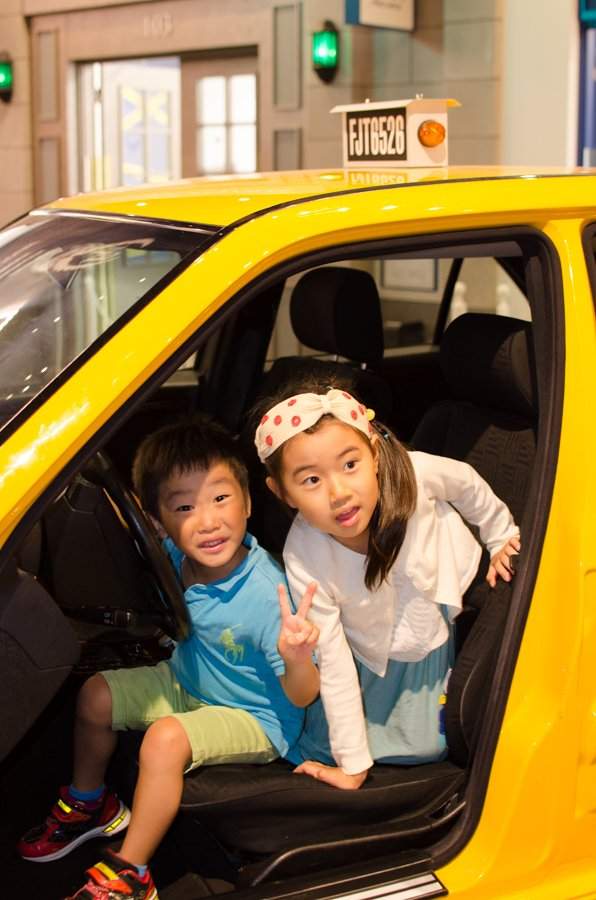 2 kids looks for passengers in a yellow NYC taxi.