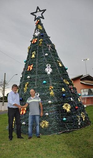Paganini e Silva posam para foto na árvore montada na entrada da cidade (Divulgação)