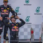 Red Bull Racing's Australian driver Daniel Ricciardo drinks champagne from his shoe as he celebrates his victory on the podium next to third-placed Mercedes AMG Petronas F1 Team's German driver Nico Rosberg (R) and second-placed Red Bull Racing's Belgian-Dutch driver Max Verstappen after the Formula One Malaysian Grand Prix in Sepang on October 2, 2016.  / AFP PHOTO / PEDRO UGARTE