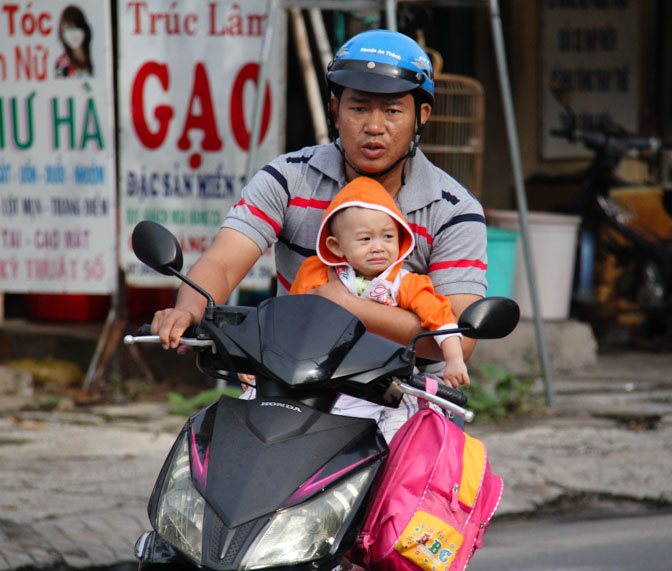 A Vietnamese man driving a scooter while holding a baby that isn't wearing a helmet.