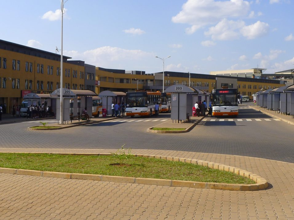 Passengers board buses, the service of which was improved with the Smart Kigali initiative.
