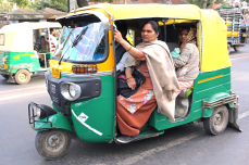 Rickshaw in India with woman passenger in orange traditional clothing