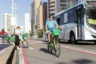 Ana Nassar of ITDP Brazil on bike from Fortaleza bikeshare, Bicicletar, with Fortaleza bus in the background