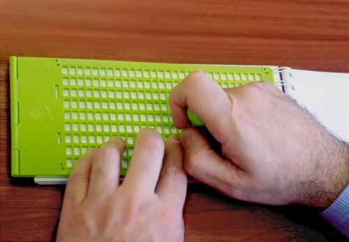 detalle de las manos de una persona escribiendo en braille