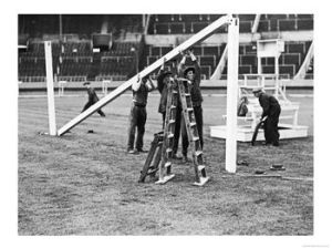 "Goal posts being installed at Wembley stadium before the 1936 Football Association Challenge Cup Final between Arsenal and Sheffield United.  Wooden crossbars and uprights were used to make football goals in the days before extruded aluminum. In the background is the podium where a conductor in a white suit used to lead community signing before the footballers anthem"" Abide with Me"" as the finale before kick off."