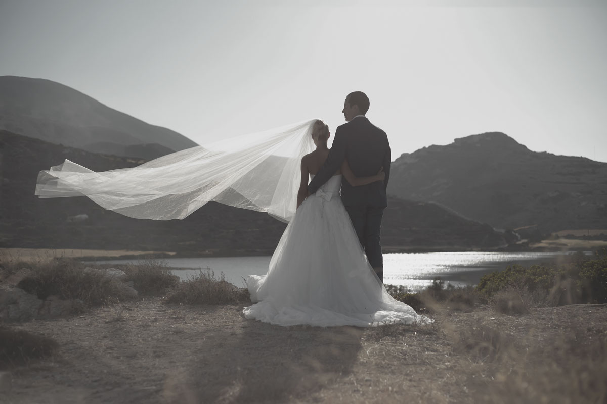 a bridal couple at the edge of a lake