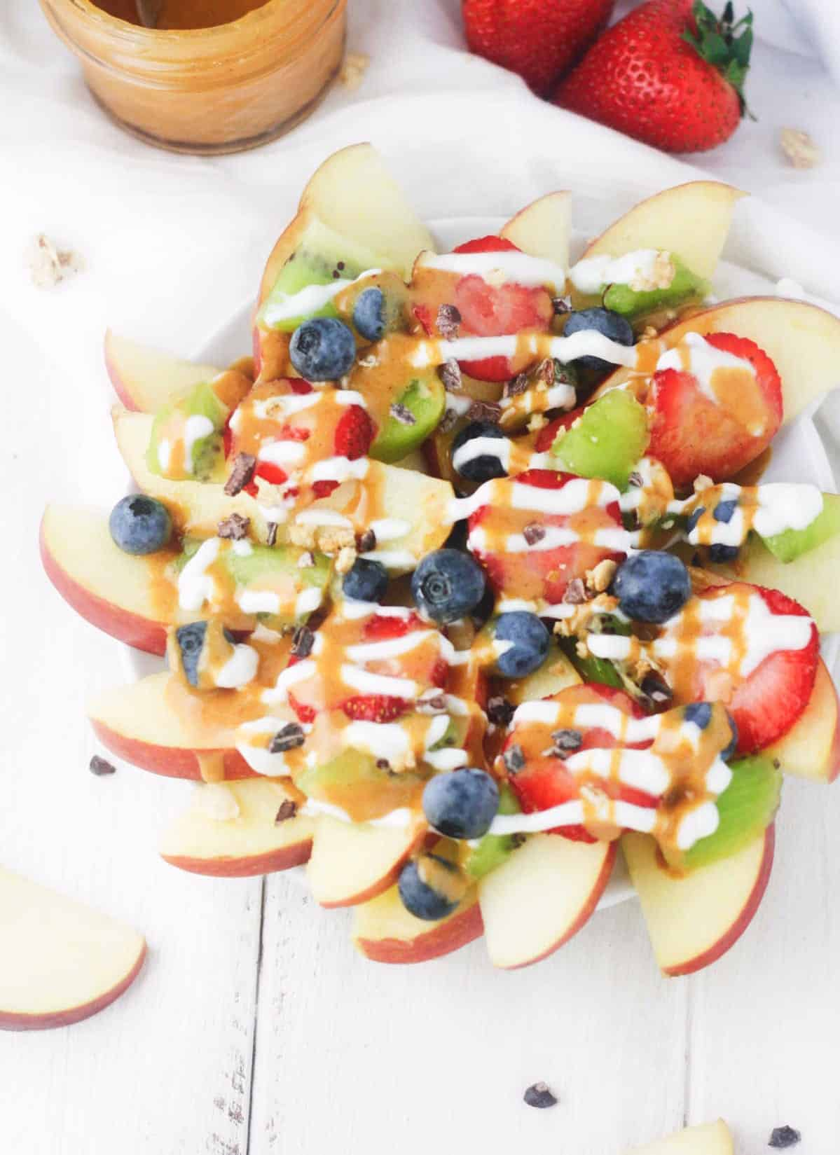 Easy Loaded Fruit Nachos. The perfect game day/movie night/anytime snack! Apple nacho slices, topped with a variety of fresh fruits, cacao nibs, granola and drizzled with Greek yogurt and a low calorie peanut butter maple drizzle. DOES IT GET BETTER?! www.itscheatdayeveryday.com