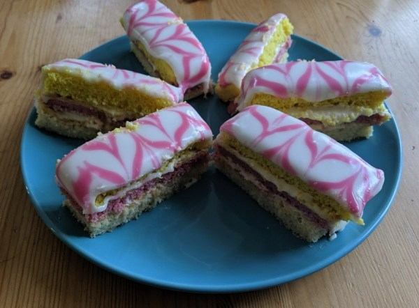 Six angel cake slices with pink and while feathered icing sit on a blue plate. They all look wonky and different sizes.