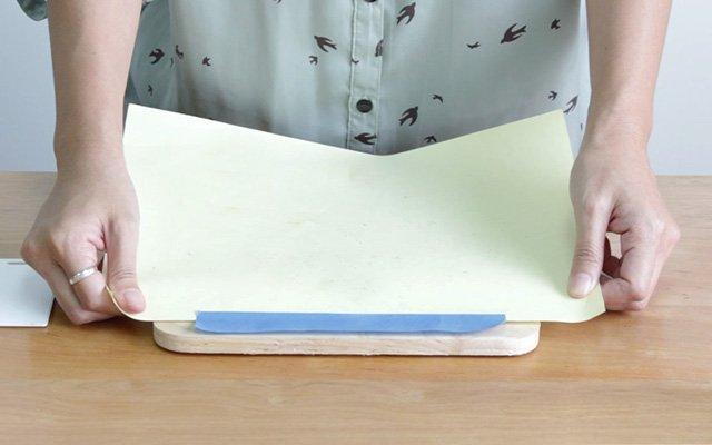 วางกระดาษลงบนแผ่นไม้