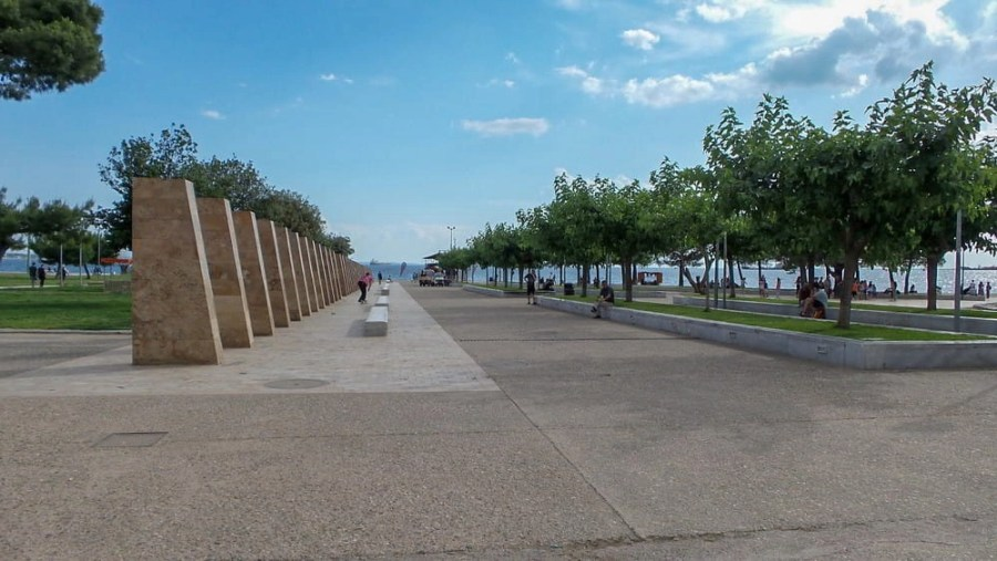 Trees and the sea at the White Tower Square in Thessaloniki, Greece.
