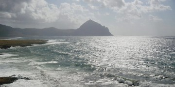 Waves in a body of water with a mountain hill in the background.