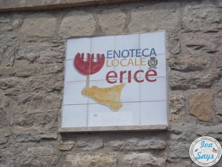Sign made of white tiles in a stone wall listing Enoteca Locale Erice (Erice, Sicily).