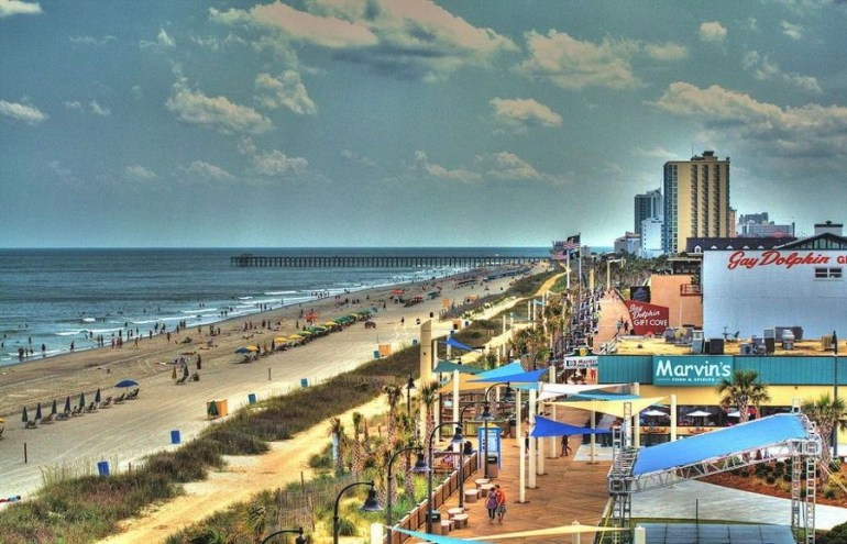 The shoreline at Myrtle Beach in South Carolina filled with people at the beach and hotels along the boardwalk.