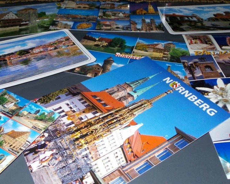 Different postcards laid out on a table. Postcard of Nuremberg, Germany is first on the pile.