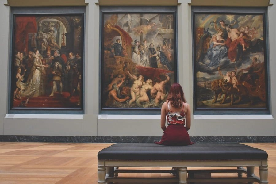 A woman sitting inside a museum and looking at three paintings hanging on a wall in the museum.