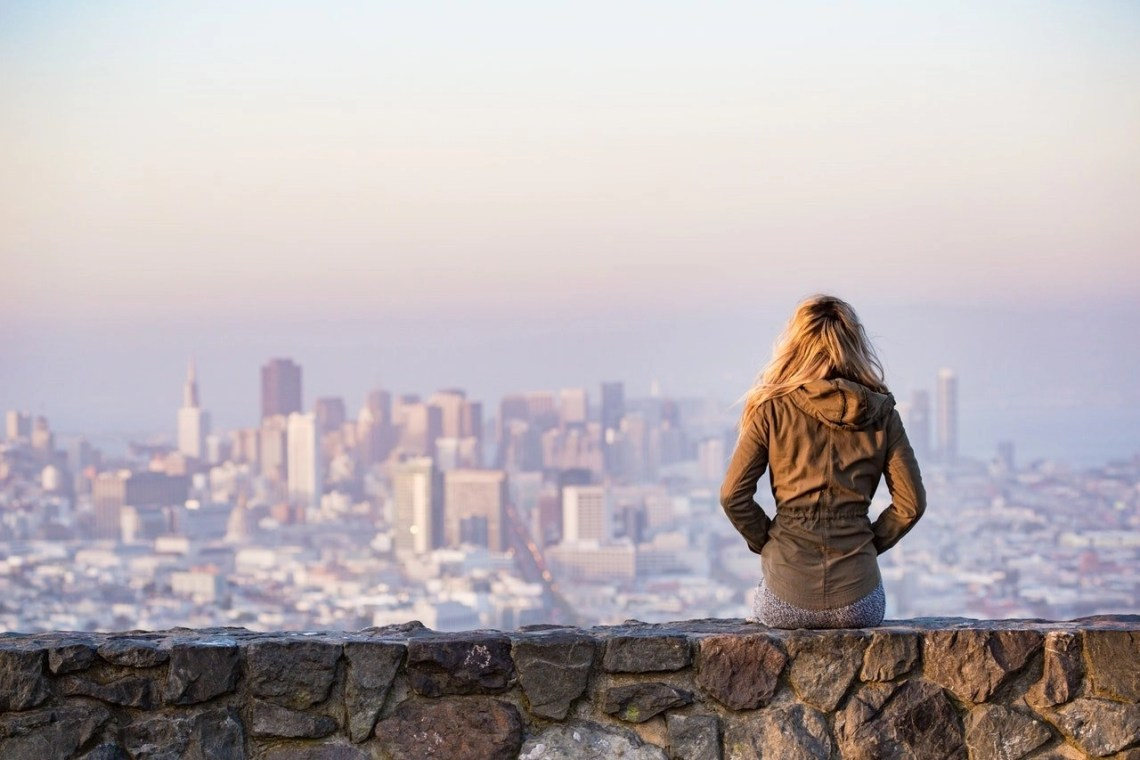"A woman resting on a small rock wall overlooking to a city in the distance. Feature image for the blog post ""Big Buildings, Small Cost: Getting The Most Out Of A City Break"" on ivasays.com"