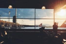 People waiting at an airport gate for a flights and looking out the windows to a Swiss Air plane.