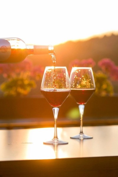 A bottle of red wine being poured into one of two red wine glasses (both are half filled) with a flower field in the background.