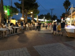 A restaurant or a taverna that has all its outside tables filled with customers and people walking on the street by it.