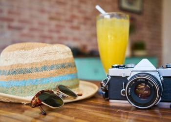 Travel accessories - sunglasses, straw hat, and camera - places on a coffee table next to a mimosa or orange juice drink.