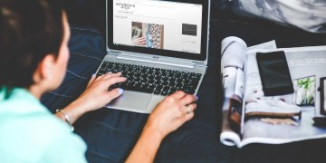 "A women working on laptop on a interior design blog with a magazine next to the work space. Learn how to improve your blog and blogging content in this article ""Beat The Blogging Competition With Style."""