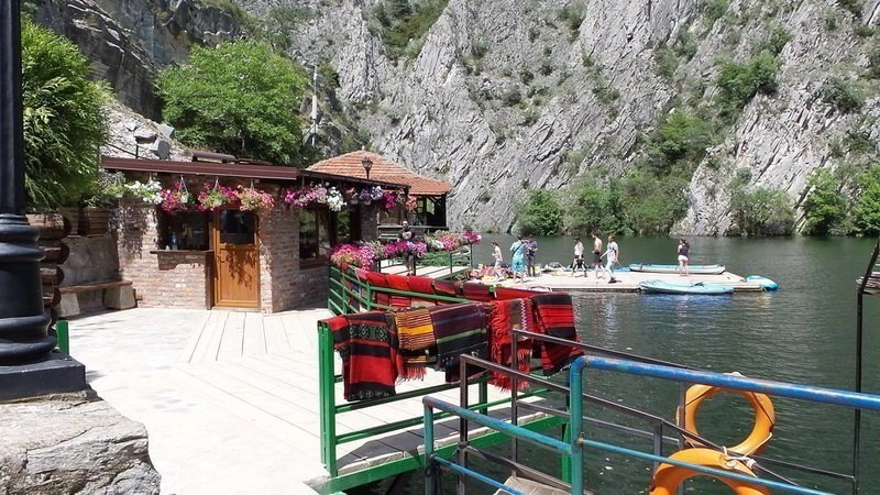 Traditional Macedonian red wool rugs on a green railing by the Canyon Matka water. People on kayaks in the Matka lake.