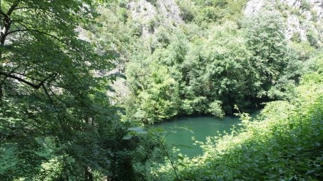 Big gorges, green trees, and a view to the water body in canyon Matka, Macedonia from the entrance of cave Vrelo.